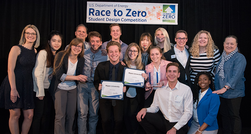 "Miami University participants who took part in the 2018 Race to Zero Student Design Competition pose with their award certificates. A banner in the background reads, ""U.S. Department of Energy Race to Zero Student Design Competition"" and has the Race to Zero logo."