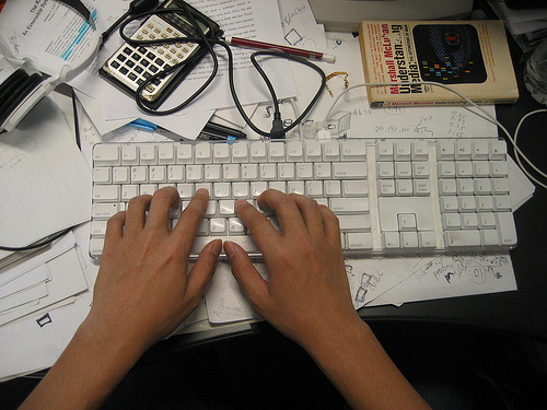 "Hands type on a computer keyboard that is on top of and surrounded by various papers. A calculator, pencil, a highlighter, and a copy of Marshall McLuhan's ""Misunderstanding Media"" are also visible."
