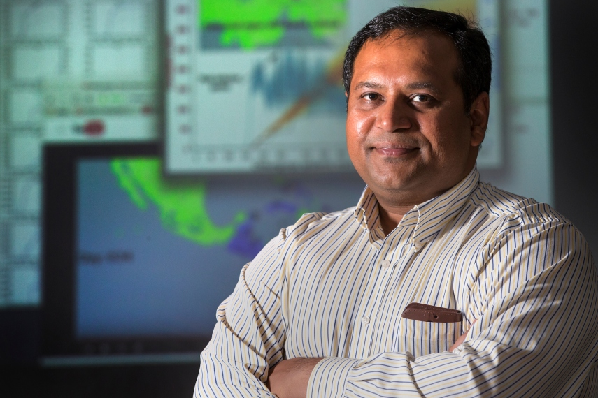 DJ Rao stands in front of a screen displaying computer-generated models of Zika virus epidemiology.