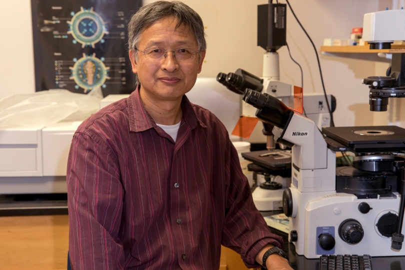 Xiao-Wen Cheng sits in front of a microscope in his lab.
