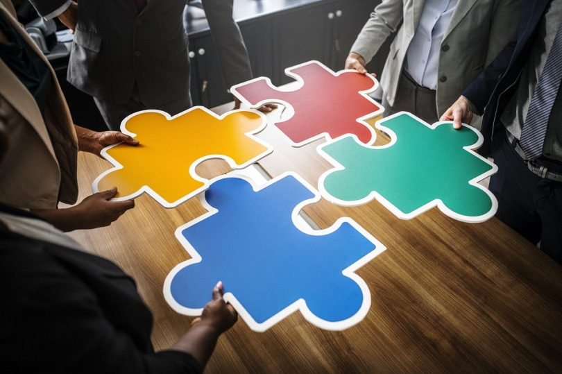 Four people, each holding an oversized puzzle piece, fit the pieces together.