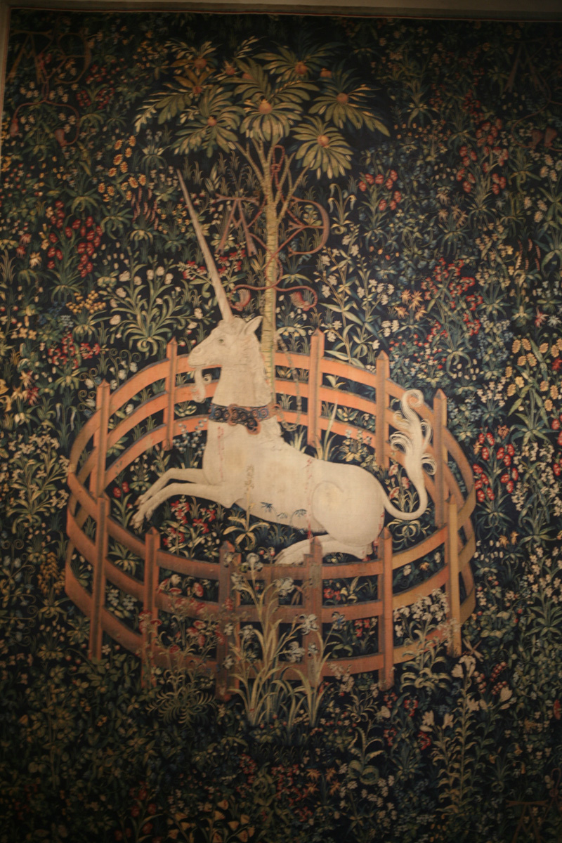 Tapestry depicting a unicorn within a circular fence situated in a field of flowers.