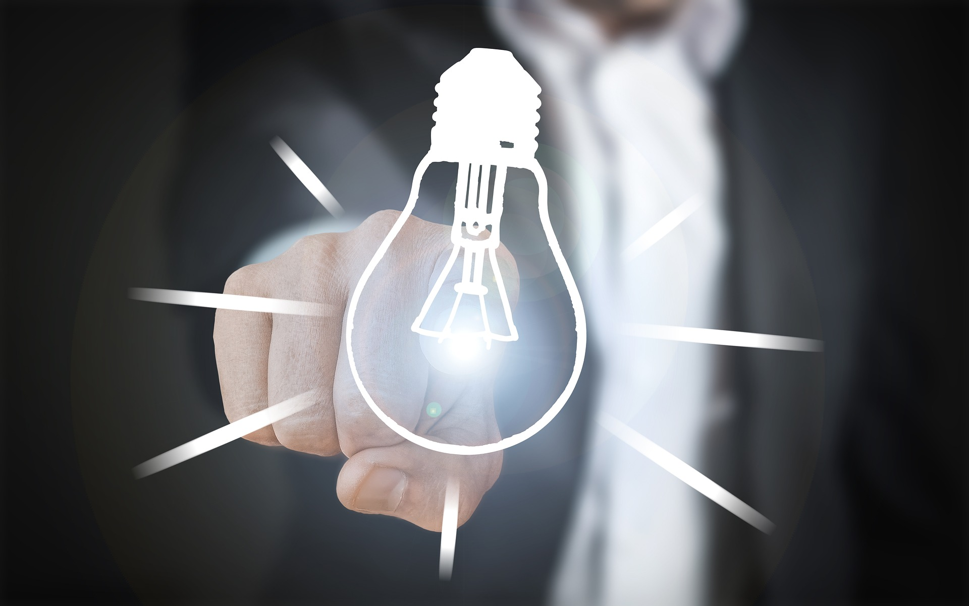 A man wearing a business suit touches a drawing of an illuminated lightbulb.
