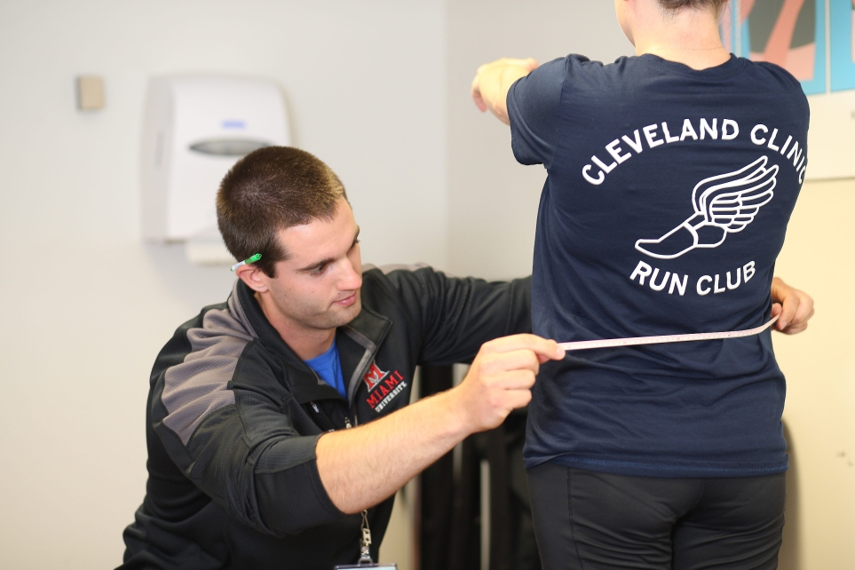 A Miami University student intern takes measures the waist of a research study participant.
