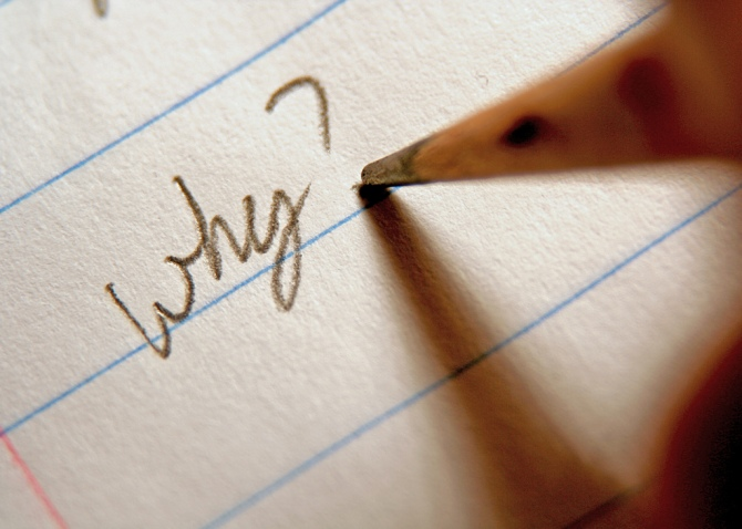 "A pencil writes the word ""why"" and a question mark on a piece of notebook paper."