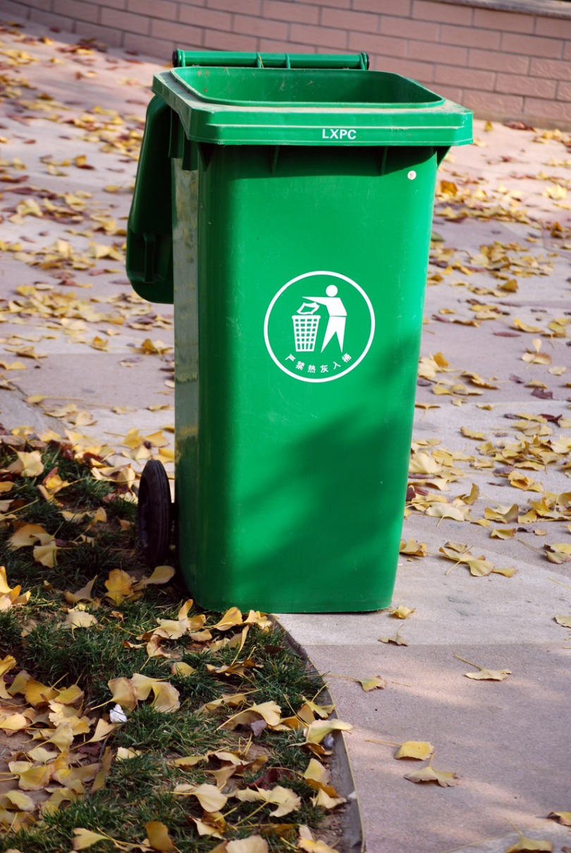A green recycling bin sits on a sidewalk.