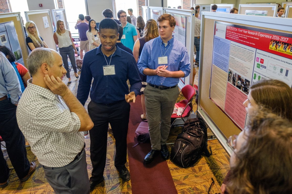 Students presenters discuss their poster with an Undergraduate Research Forum attendee.