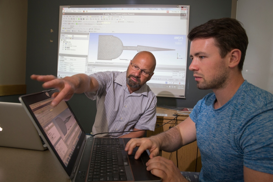 Jens Mueller and a student look at data on a computer screen.