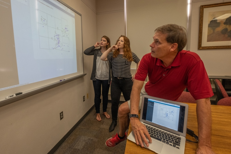 John Bailer, Bri Clements and Katherine Shockey look at a data visualization on a screen.