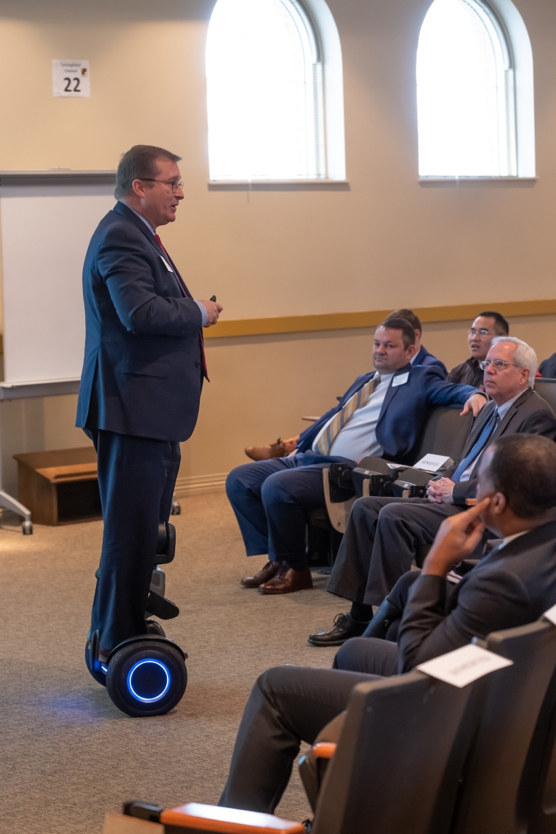 Standing on a hoverboard, Brian Cobb addresses Innovation at Miami and Beyond attendees.