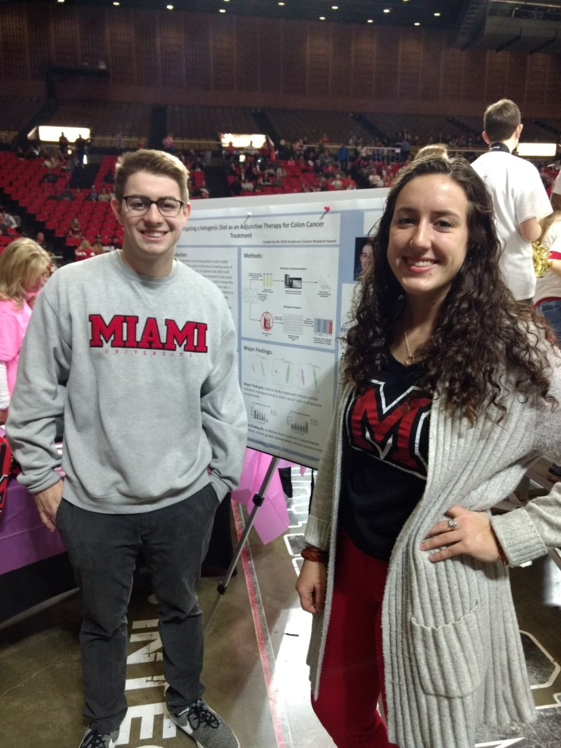 Undergraduate researchers Ryan Parnell and Danille Allaire pose in front of a poster explaining their cancer research project.