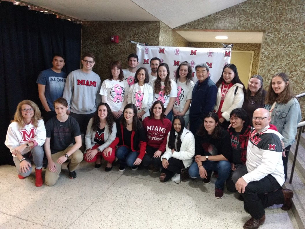 A group of students and faculty, along with President and Dr. Crawford pose for a photo in front of a Love.Honor.Care photo backdrop in Millett Hall.