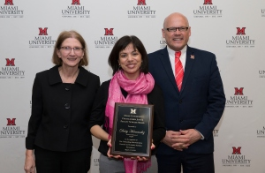 Daisy Hernández, flanked by Provost Phyllis Callahan and President Greg Crawford, poses with a plaque commemorating her Distinguished Junior Faculty Scholar Award.