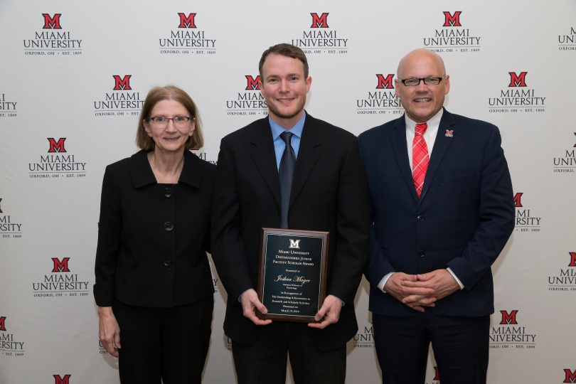 Josh Magee, flanked by Provost Phyllis Callahan and President Greg Crawford, poses with a plaque commemorating his Distinguished Junior Faculty Scholar Award.