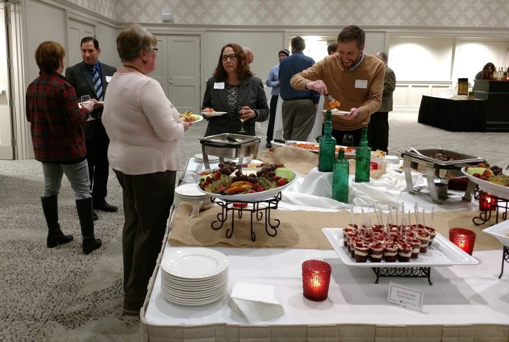Attendees at the reception help themselves to appetizers on the buffet.