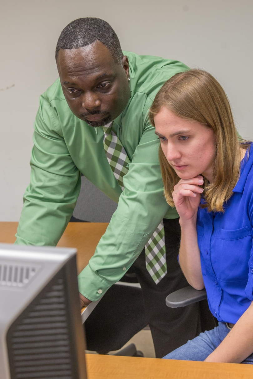 Professor Jay Smart and a student look at a screen during testing related to psychology research.
