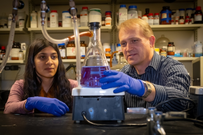 DJ Ferguson and Jyoti Kashyap work with liquid in a flask in Ferguson's lab.