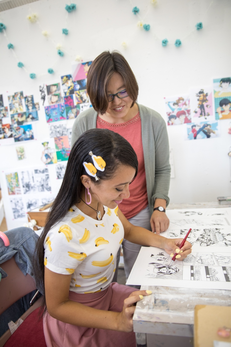 Student Selina Davis works on a drawing while her faculty sponsor, Associate Professor of Art Joomi Chung, looks on.