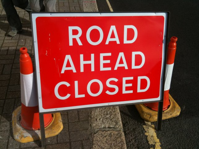 """Road Ahead Closed"" sign on a street, flanked by orange traffic cones."