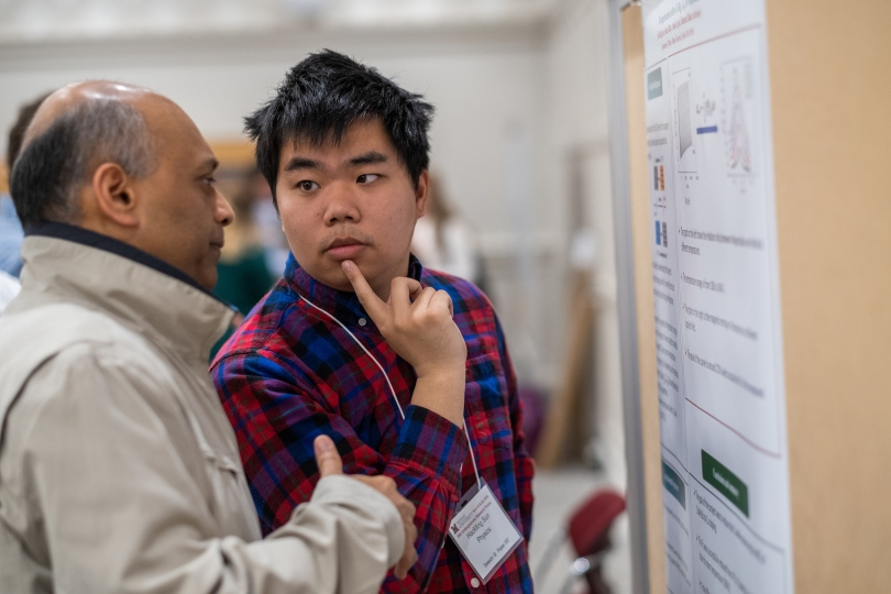 An undergraduate student researcher discusses his poster with an Undergraduate Research Forum attendee.