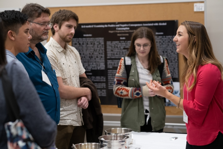An undergraduate student researcher discusses her work with attendees at the 25th Annual Undergraduate Research Forum