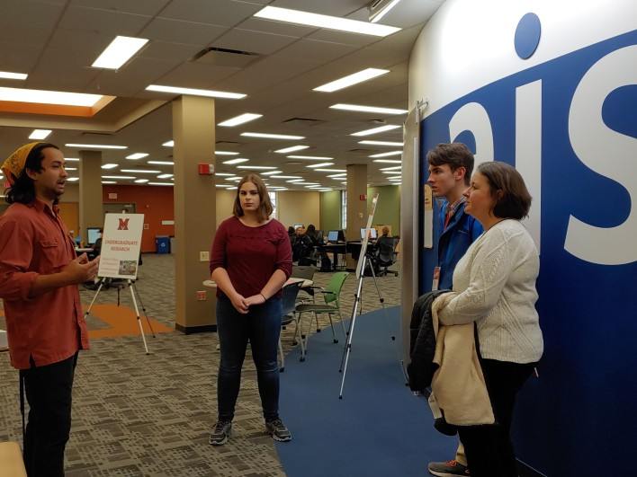 An undergraduate researcher talks to an accepted student and his mother.
