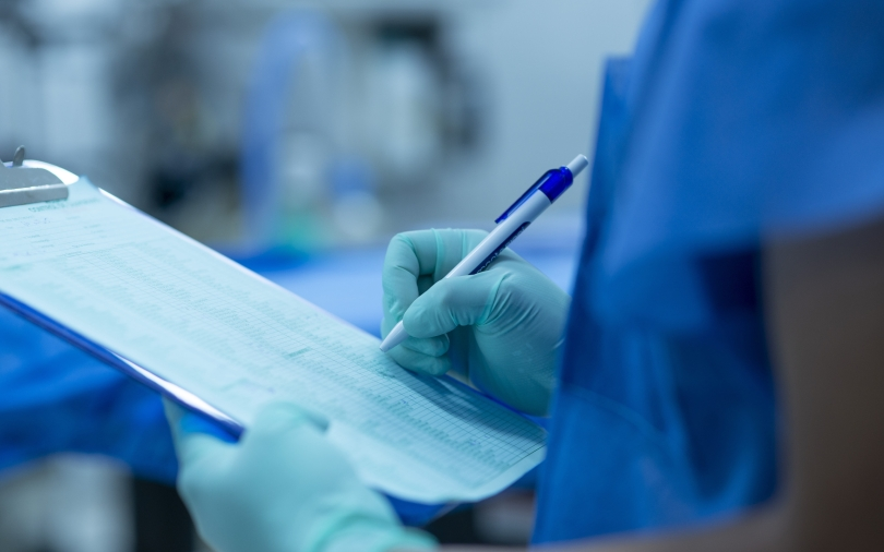A health care provider wears surgical gloves and holds a clipboard with a checklist.