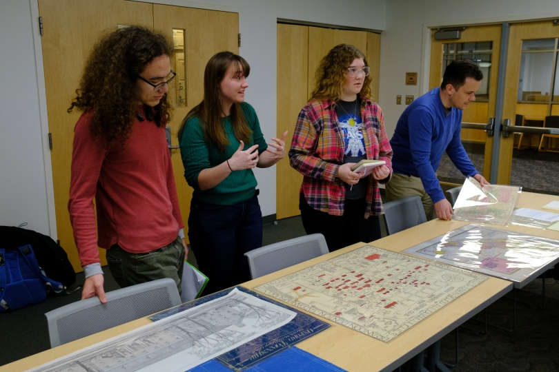 Professors and students conduct research with historical maps and schematics.