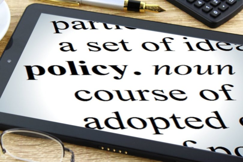 "Tablet device with the word ""policy"" and parts of the definition of the word policy visible on the screen."