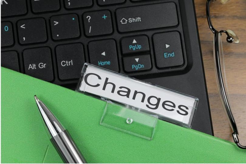 "A hanging file folder labeled ""Changes"" sits atop a computer keyboard."
