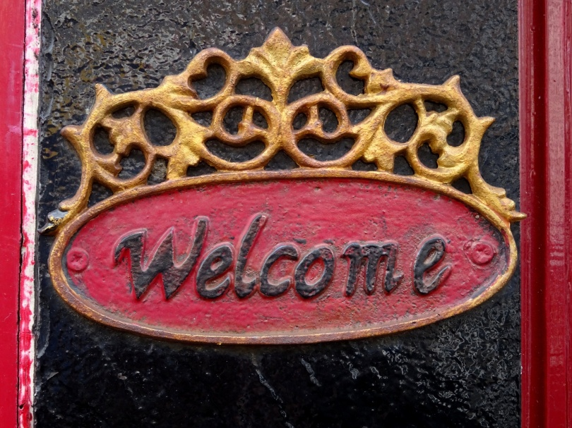 "A plate affixed to a doorway says ""Welcome."""